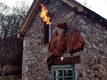 fire breathing dragin made from redwood by simon o'rourke mounted on a small stone two storey building