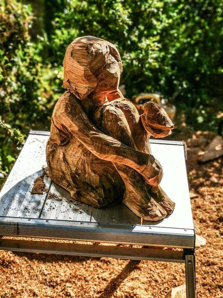 memorial sculpture for robyn by simon o'rourke in process. picture depicts a metal stool with a very basic outline carved in oak of a young girl sitting, woth a robin on her outstretched hand
