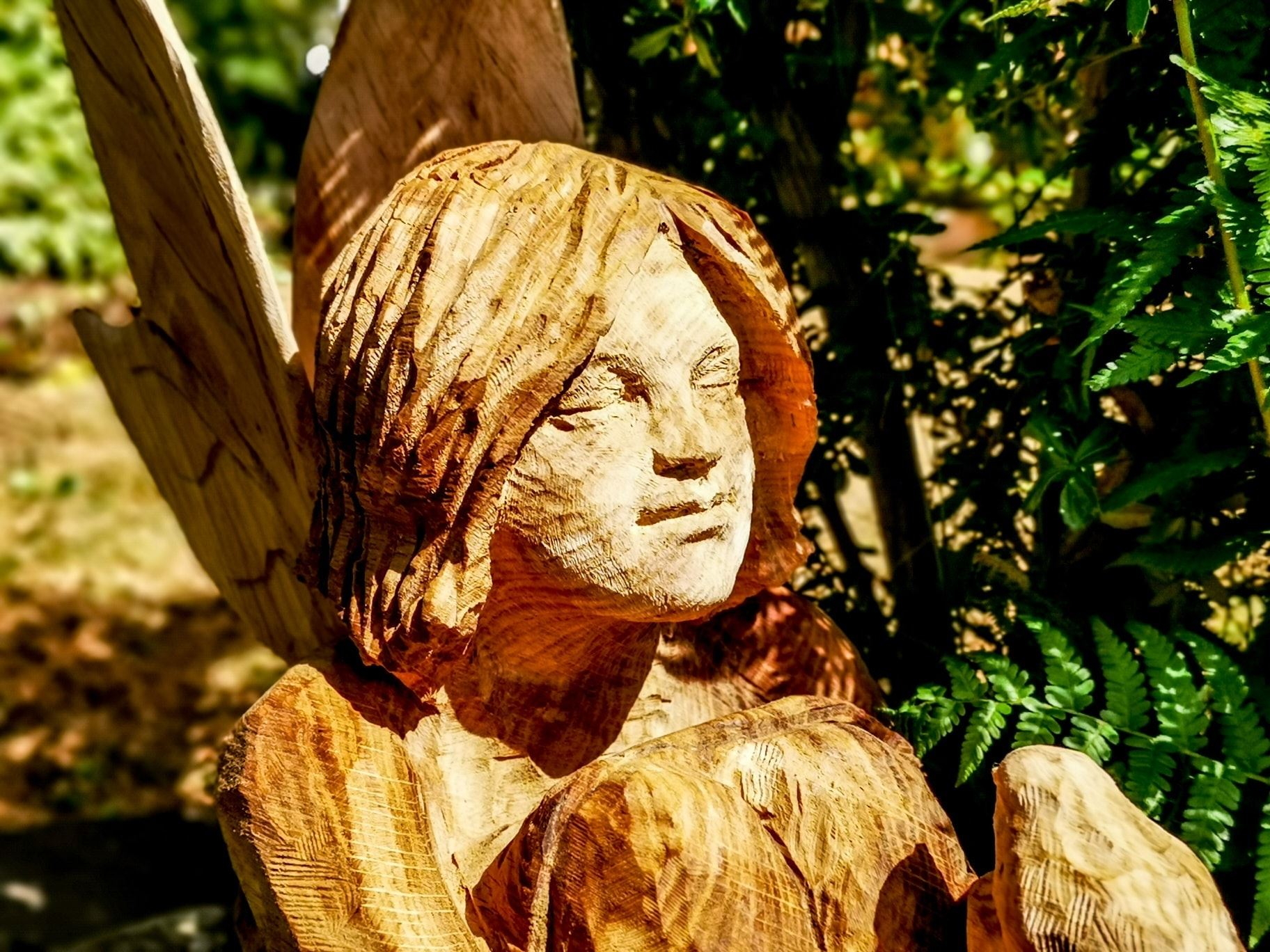 close up of the face of the oak memoral sculpture for robyn by simon o'rourke. a young girls face is shown in an oak carving with a serene expression