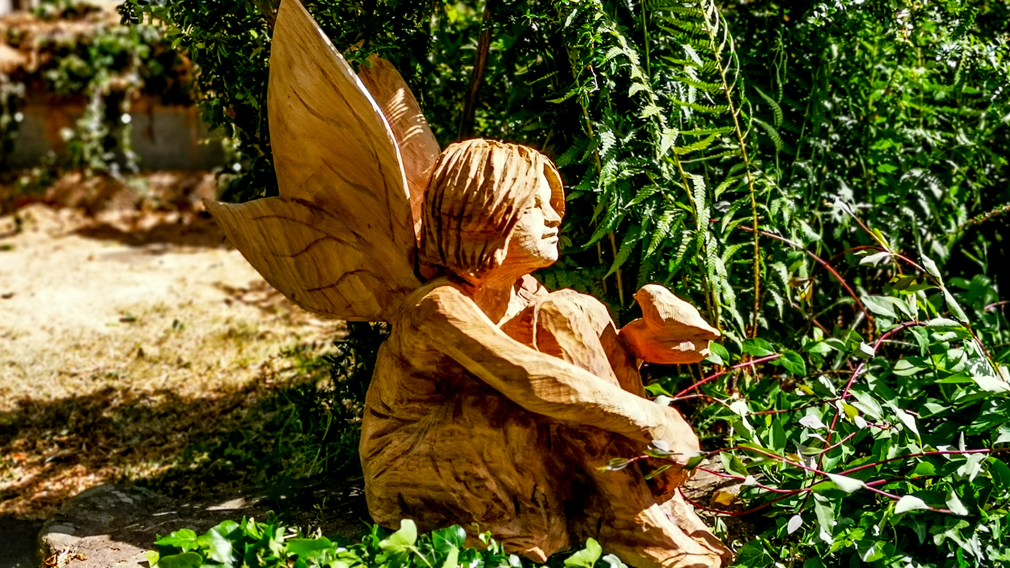 A memorial sculpture for Robyn carved by Simon O'Rourke depicting a young girl as a fairy with a robin on her open hand
