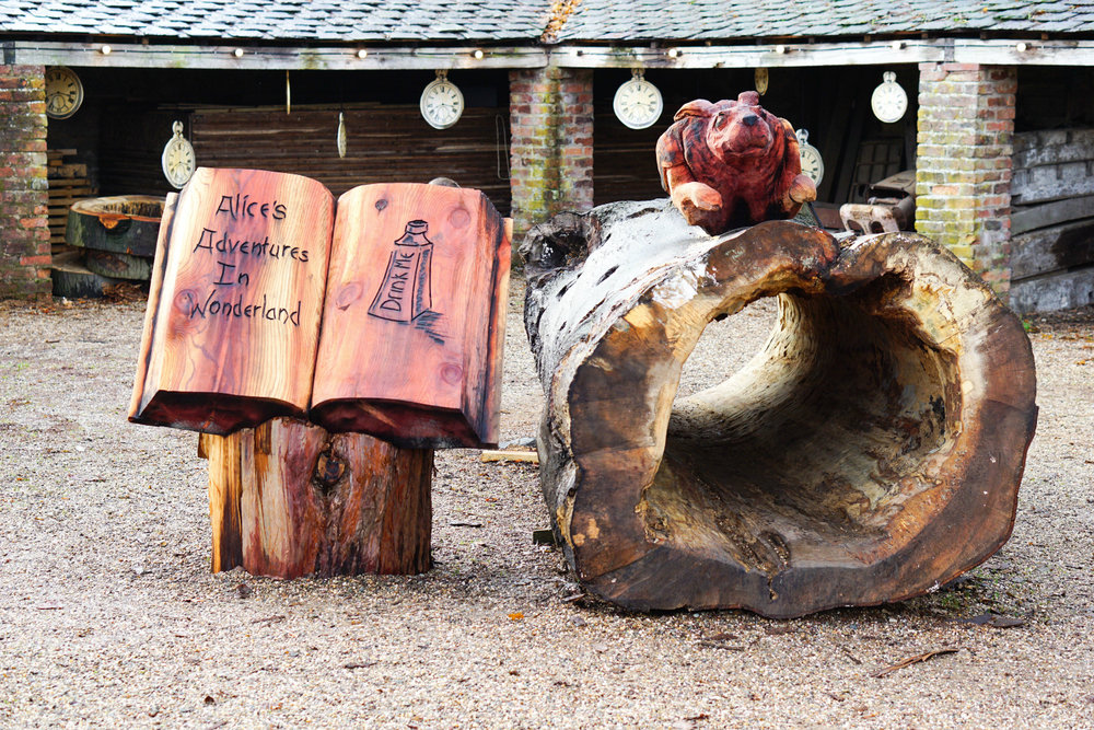 tree carving sculptures based on literature by simon o'rourke. an open book with the title alice in wonderland and the chesire cat sitting on a hollow log to the right