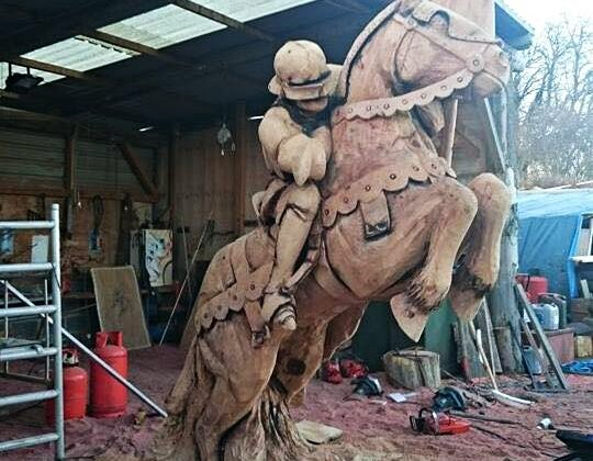life size wood carving of a knight on a rearing horse by simon orourke.Sculpture is part of a sculpture trail in Northampton.