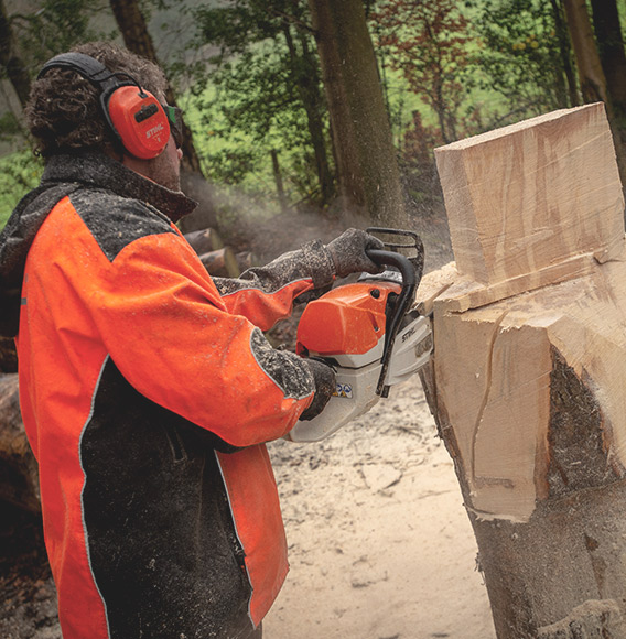 Simon O'rourke using a chainsaw to cut into wood