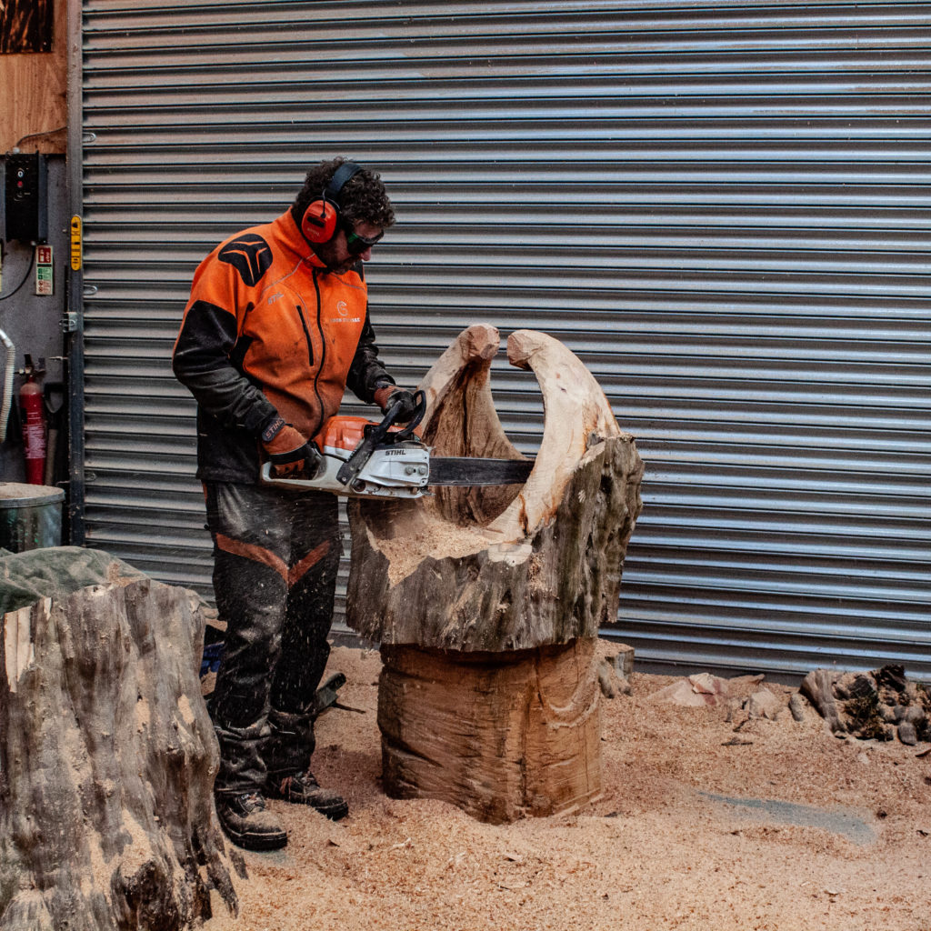 Impact of creativity and art on mental health - simon o'rourke pictured using a chainsaw to carve a dragon's mouth egg casket. He finds the process cathartic and beneficial for mental wellbeing.