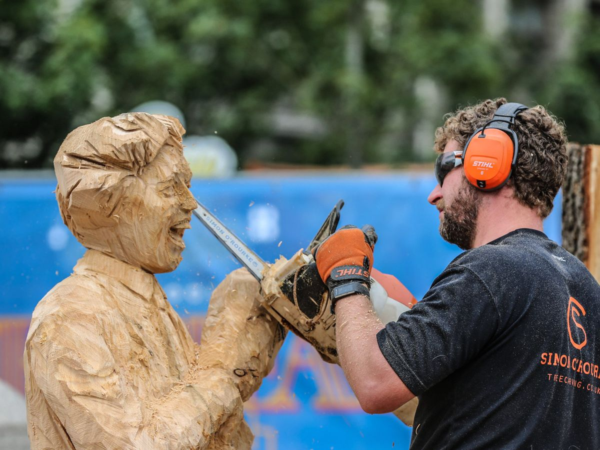 simon o'rourke carving ken dodd sculpture using chainsaw with bar in collaboration with chainsawbars.co.uk