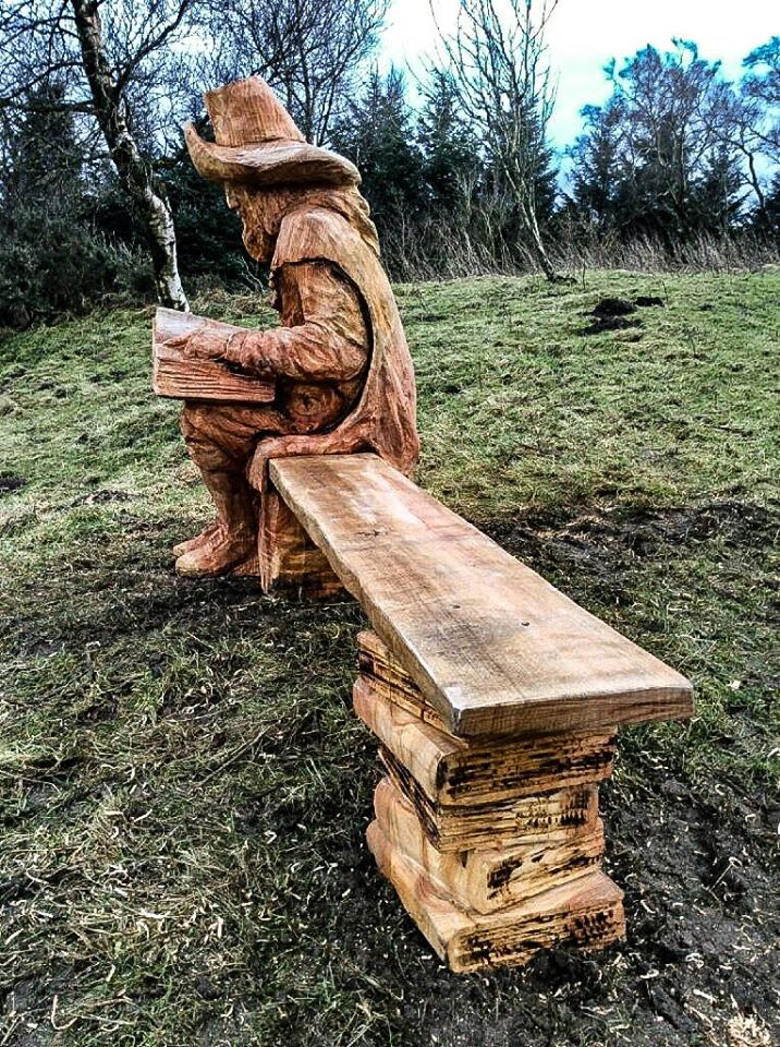Wooden sculpture portrait of a pilgrim sitting on a bench by simon o'rourke