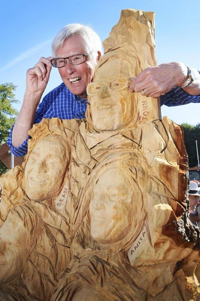 a perfect portrait for you and your family might be a collage. this photo is of a sculpture of multiple faces in one piece of wood.