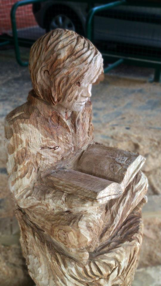 Memorial sculpture for Robyn, carved in oak, depicting a young girl reading a book