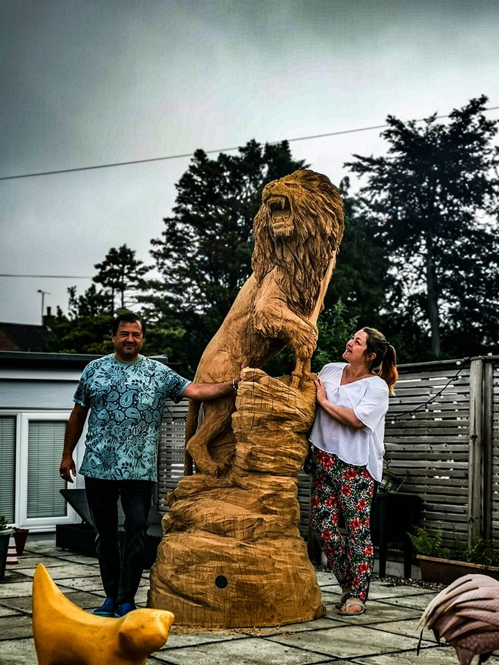 12' oak sri lankan lion sculpture by simon o'rourke pictured with the clients in a paved area