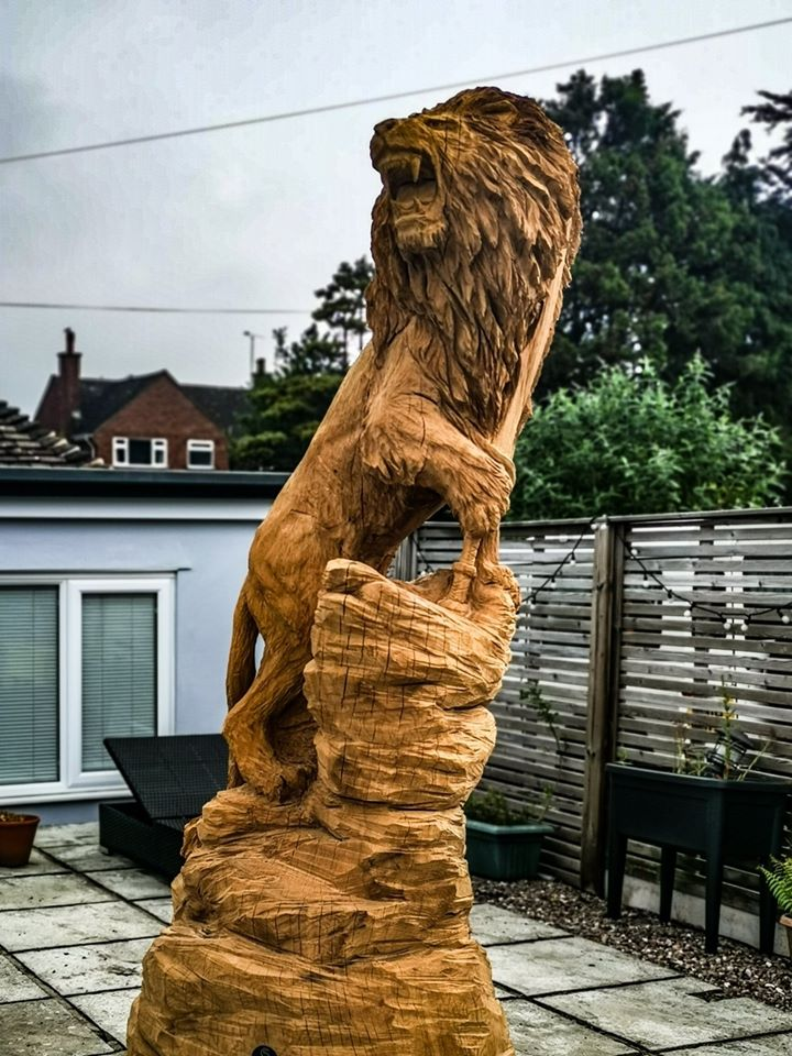 Sri Lankan Lion sculpture by simon o'rourke standing in a paved area of a private garden