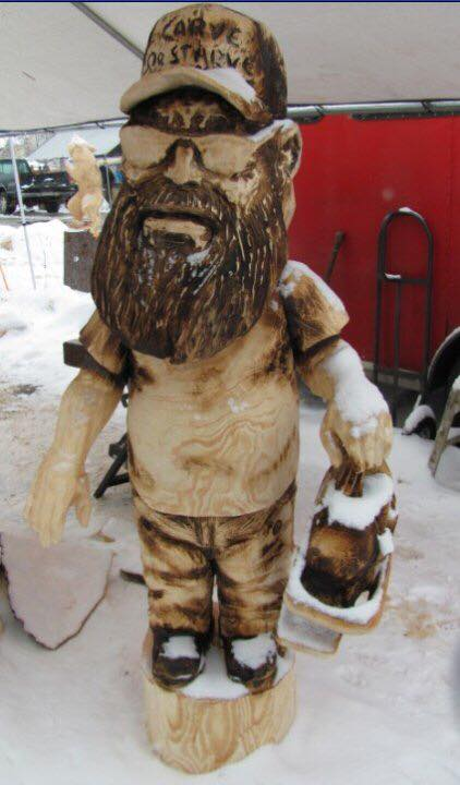 perfect portrait for you might be a bobble head like this life size carving of chainsaw artist steve backus depicted with an oversized head and carrying chainsaw carving equipment