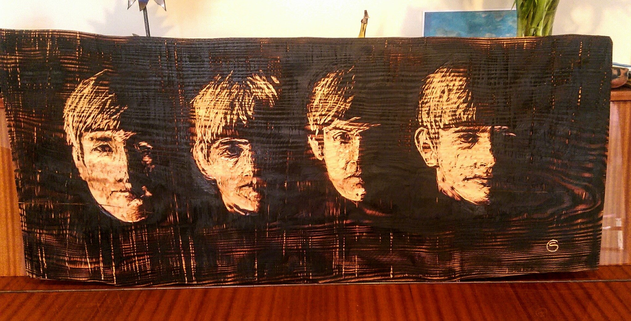 The faces of the four beatles created by simon o'rourke through burning and etching a wood panel