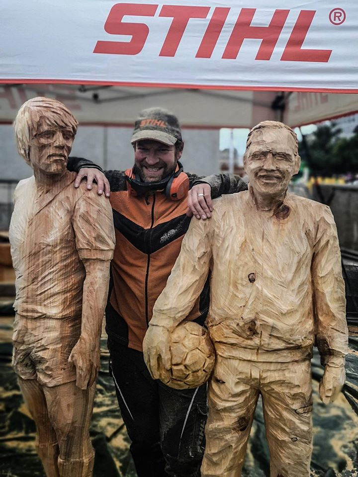 Chainsaw carving artist Simon O'Rourke standing with his life size sculptures of soccer players kenny dalglish and Bill Shankley
