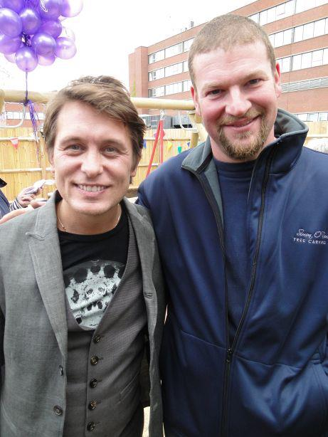 Singer Mark Owen photographed next to chainsaw carver simon o'rourke