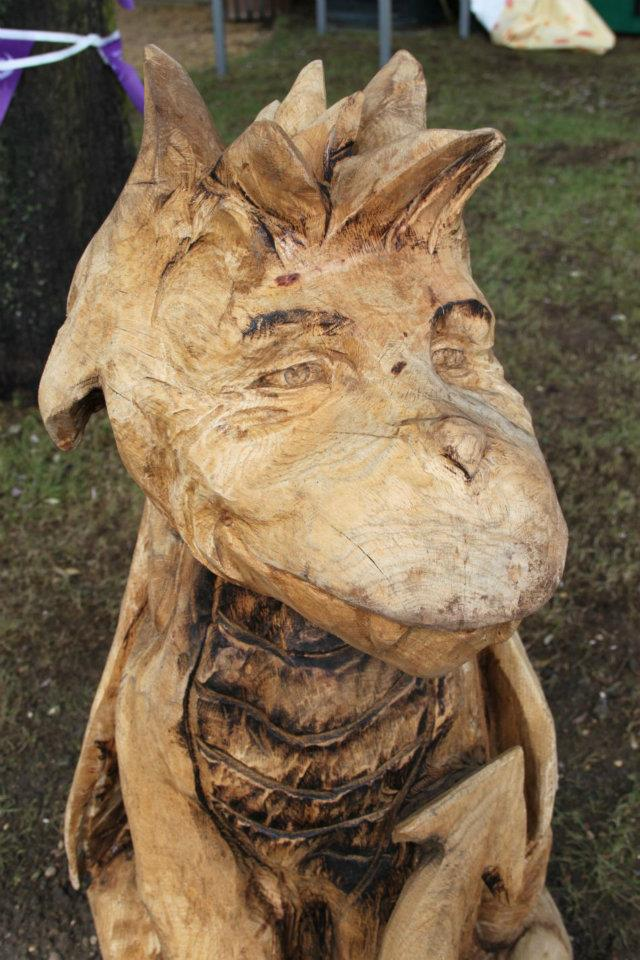 A chainsaw carved dragon by simon o'rourke in cartoon style. The dragon's face has been carved to incorporate the features of singer Mark Owen so it bears a resemblance to him