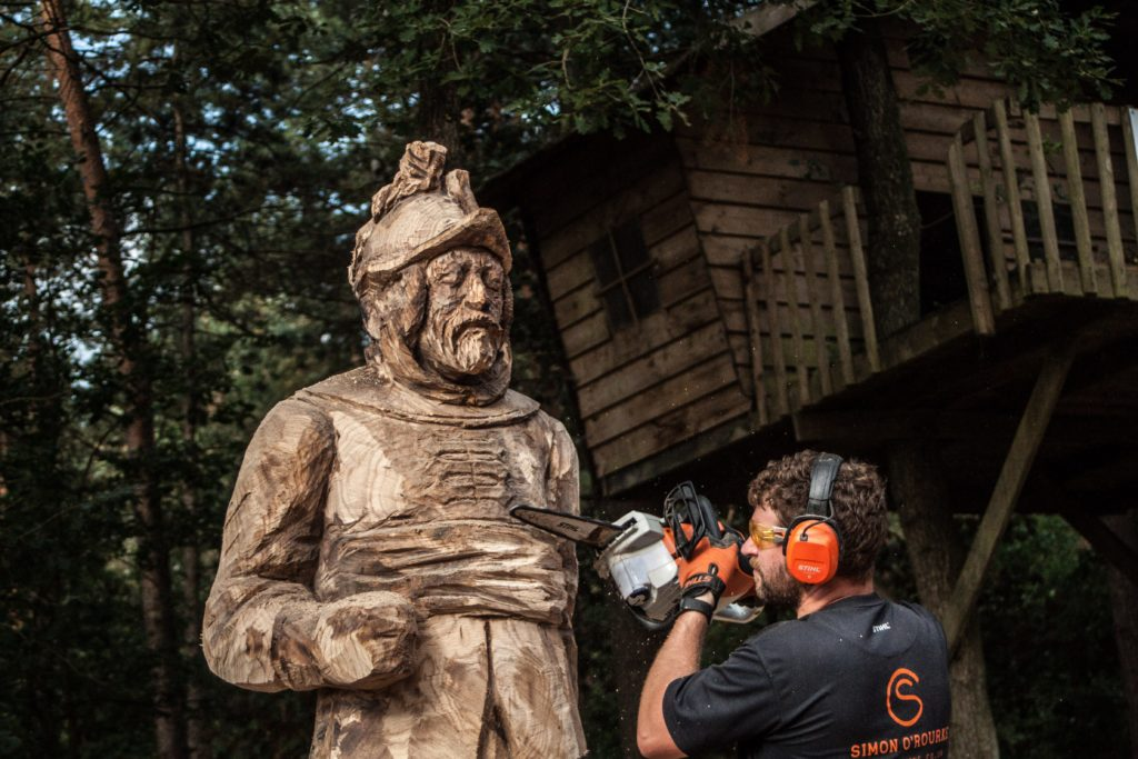 Chainsaw artist SImon O'Rourke works on a life size oak sculpture of a man