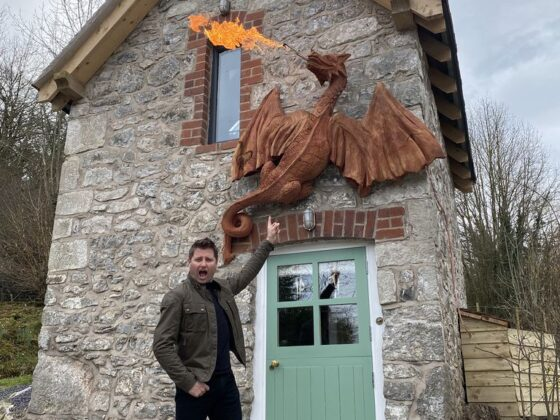TV presneter George Clarkes standing in from of a small stone building with a wall mounted fire breathing dragon made from redwood by Simon O'Rourke