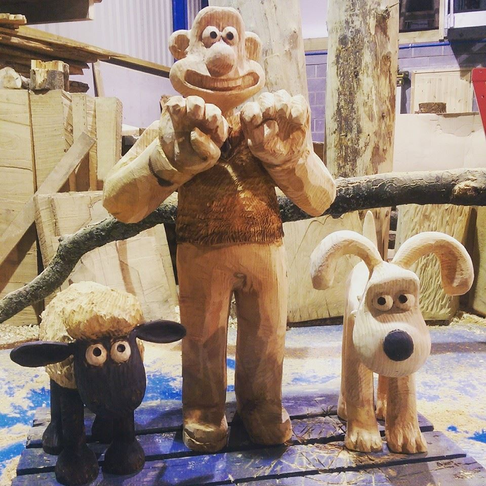 TV themed sculptures by simon o'rourke. Picture shows wooden chainsaw carved sculptures of wallace, gromit and shaun the sheep from the Nick Park series