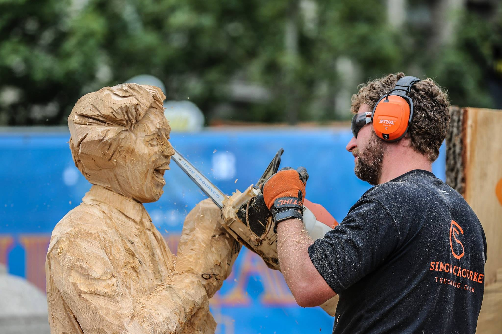 Simon O'Rourke using a chainsaw to carve a wooden sculpture of Ken Dodd