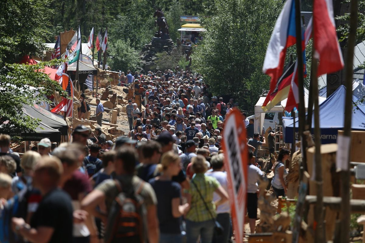 Huskycup through the years: crowds entirely fill a path in the woodland with chainsaw artists set up in booths alongside the path, carving various dragons