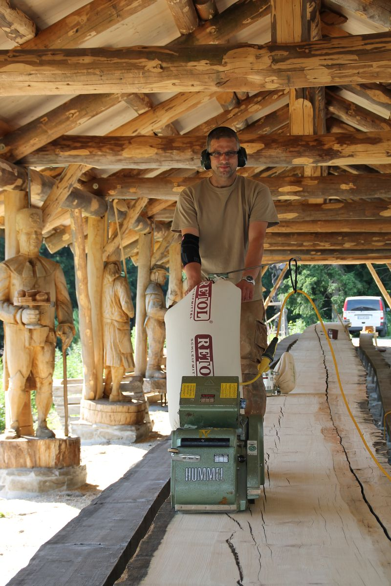 life size miners created by various chainsaw artists act as pillars for a canopy over a 40m table while a man sands the table