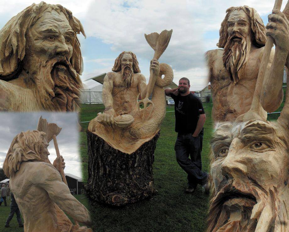 english open chainsaw competition entries by simon o'rourke. Photo shows simon standing with a 10' sculpture of neptune carved onto a treek trunk