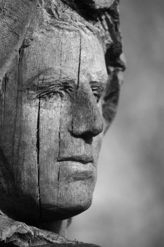 Close up of a face of a wooden sculpture showing the cracks created by weathering