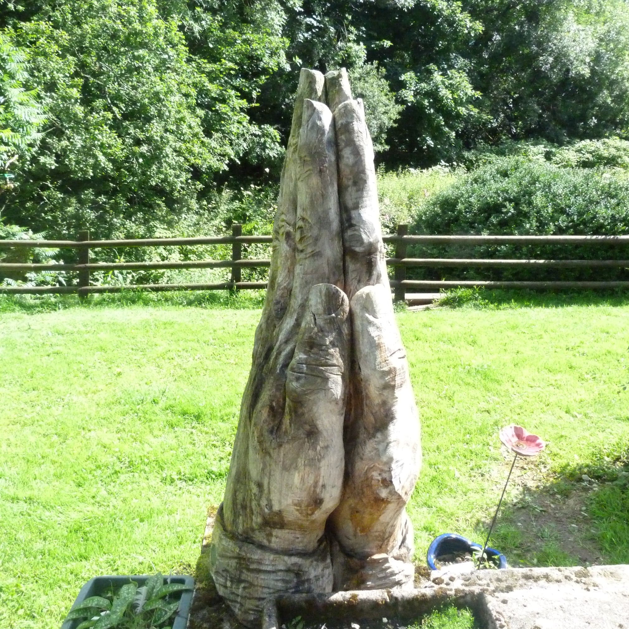 Wood or Bronze Sculpture: Picture shows large praying hands carved in oak by Simon O'Rourke. The wood has taken on grey hues due to weathering to give the hands character.
