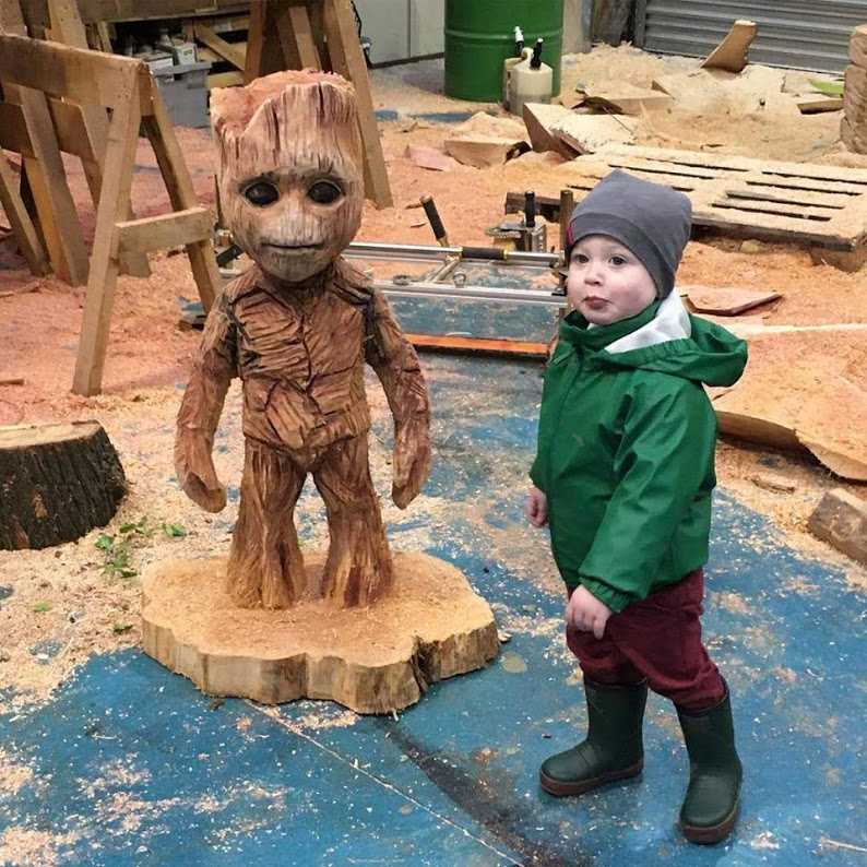Movie based sculptures: a 3' groot carved by simon o'rourke stands next to a two year old in winter clothing to show scale