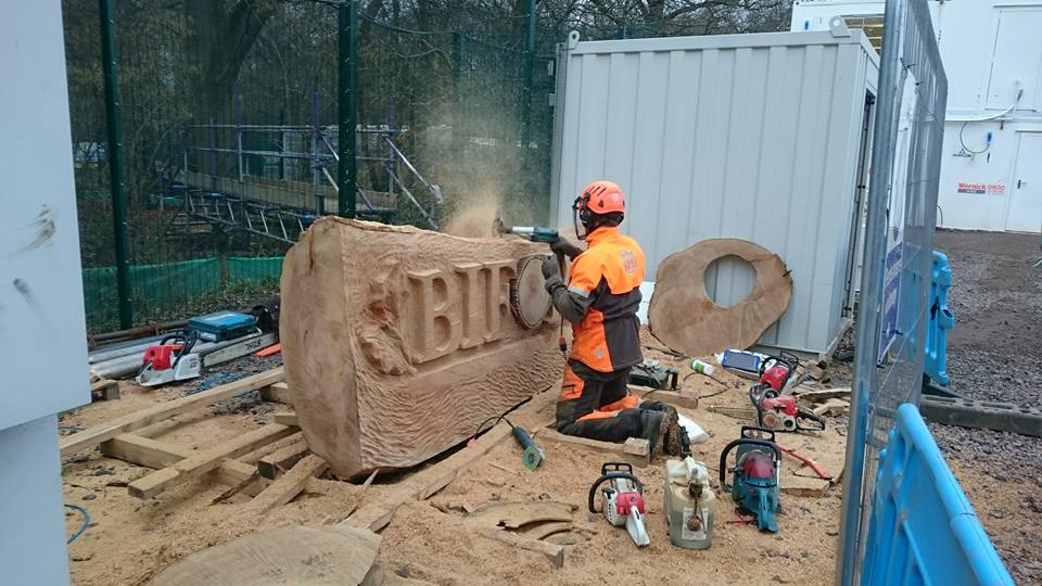 simon o'rourke kneels in front of a large piece of timber and uses a chainsaw to carve the logo for BIFOR into the wood
