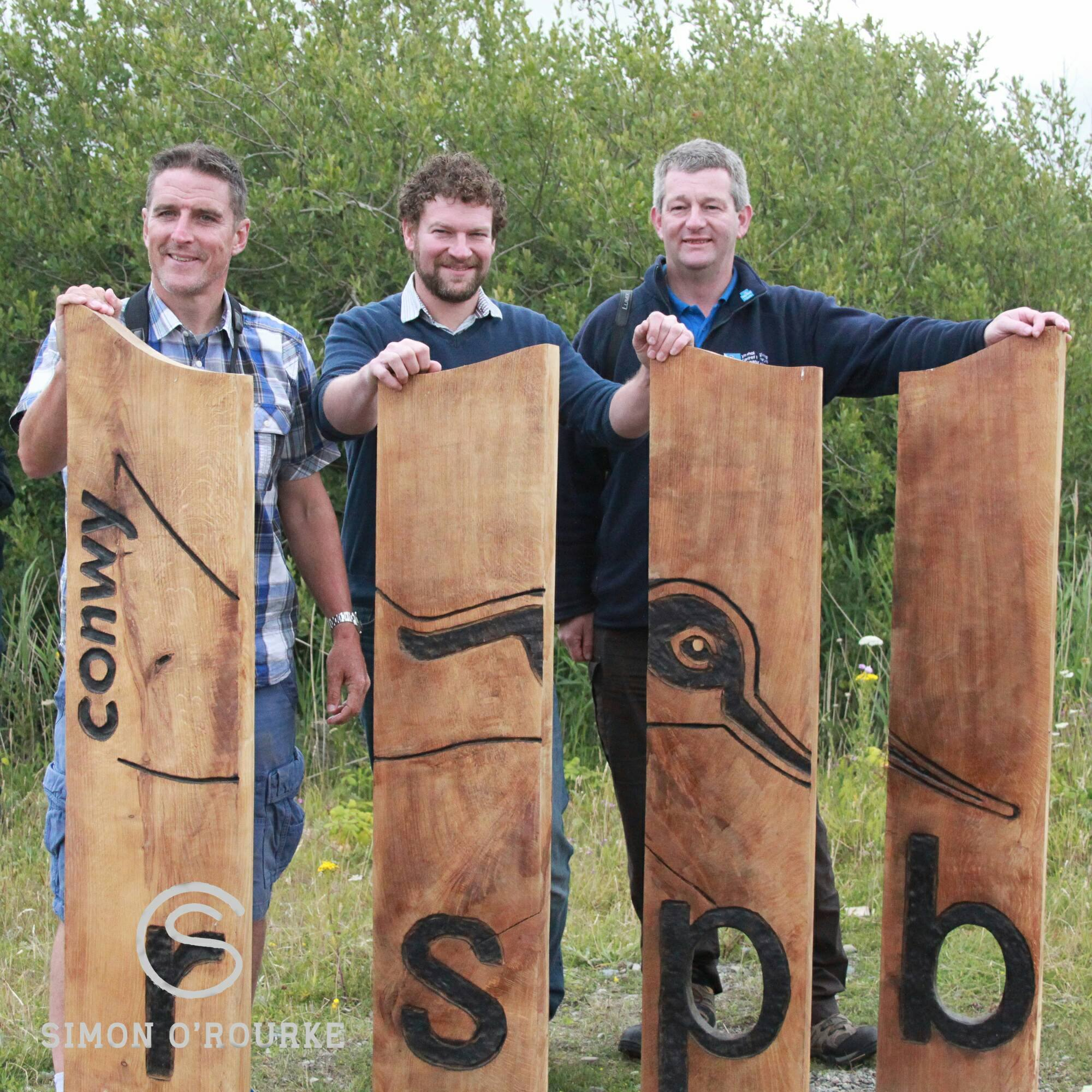 Wood logos and emblems by SImon O'Rourke: RSPB COnway. Four planks of wood stand around 4' tall with a bird and RSBP burned onto them. Three men stand behind the sign.