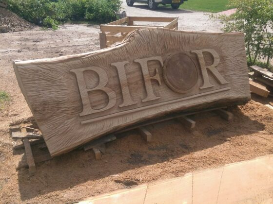 Wood logos and emblems by simon o'rourke. A large piece of timber stands horizontally with the logo for BIFOR carved inti it by simon o'rourke