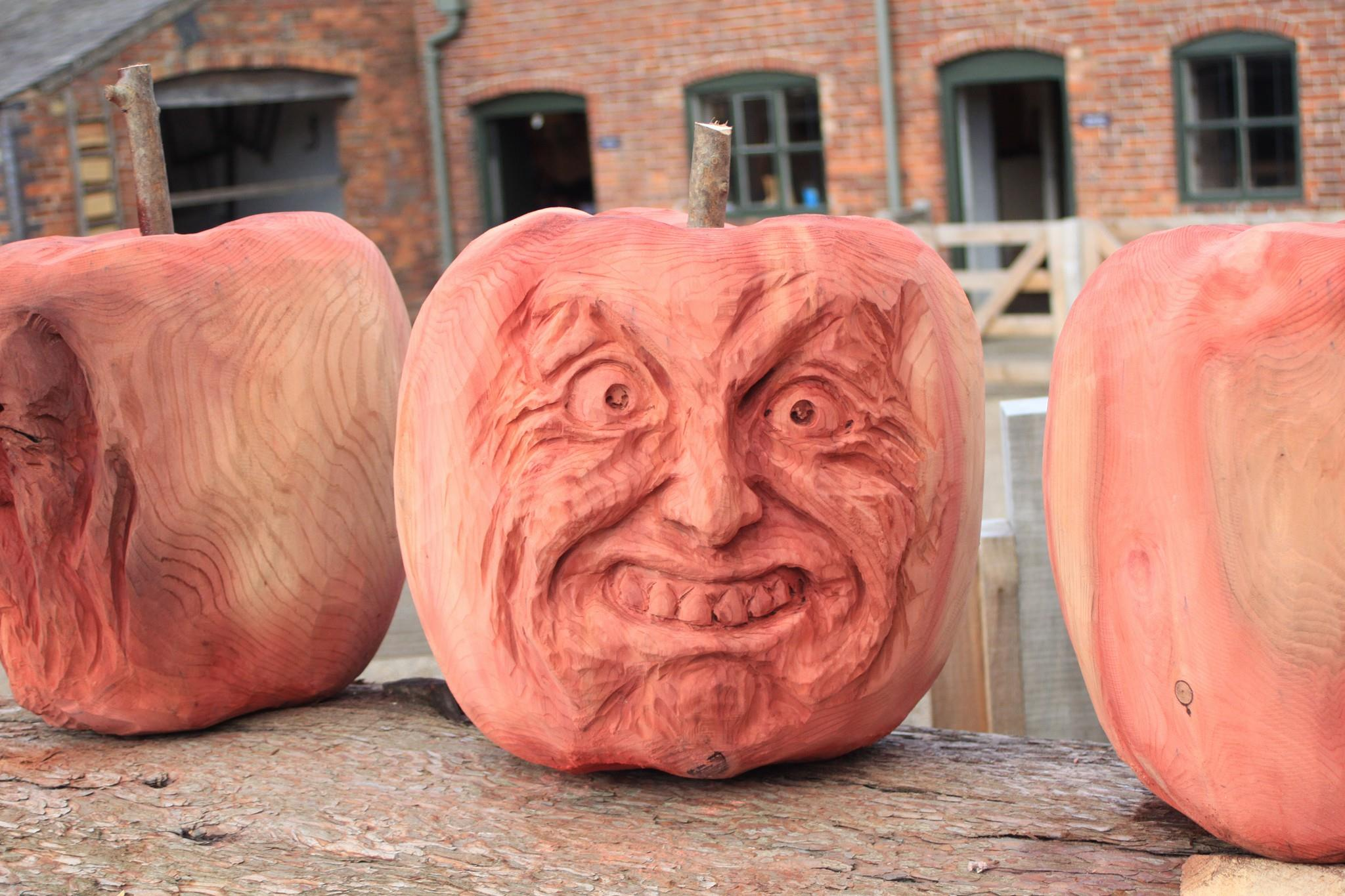 a wooden apple is carved to look like a halloween pumpkin. part of the erddig apple sculpture trail by simon o rourke