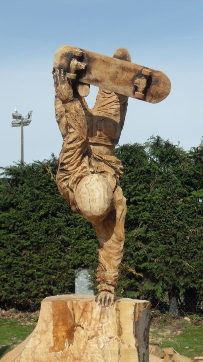 wooden life size sculpture of a female skateboarder standing on one hand to perform a trick
