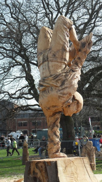 sporting sculptures made by simon o'rourke: a wooden sculpture of a female skateboarder performing a trick on one hand