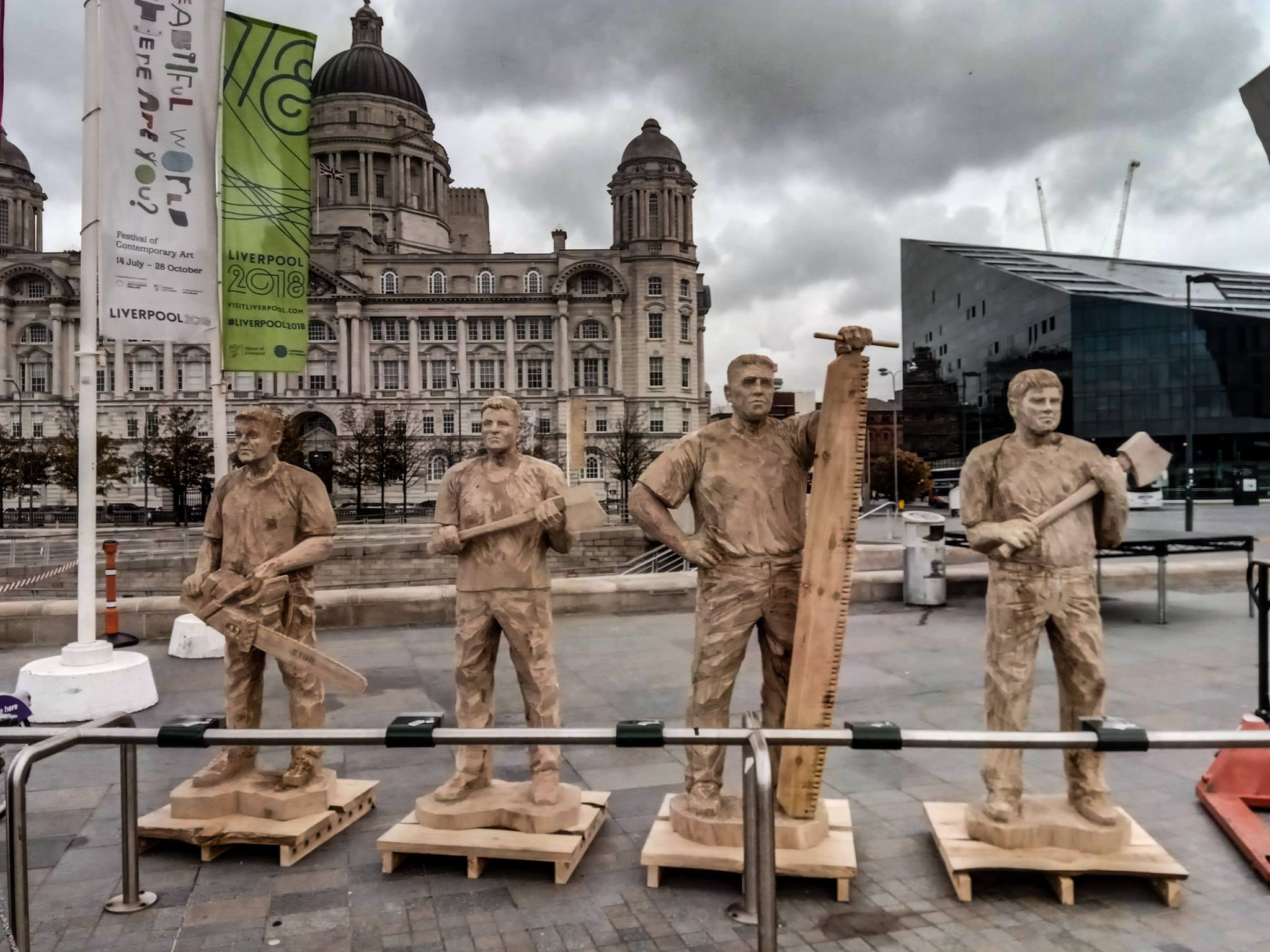 life-sized wooden sculptures of four timbersports athletes stand in front of a large building