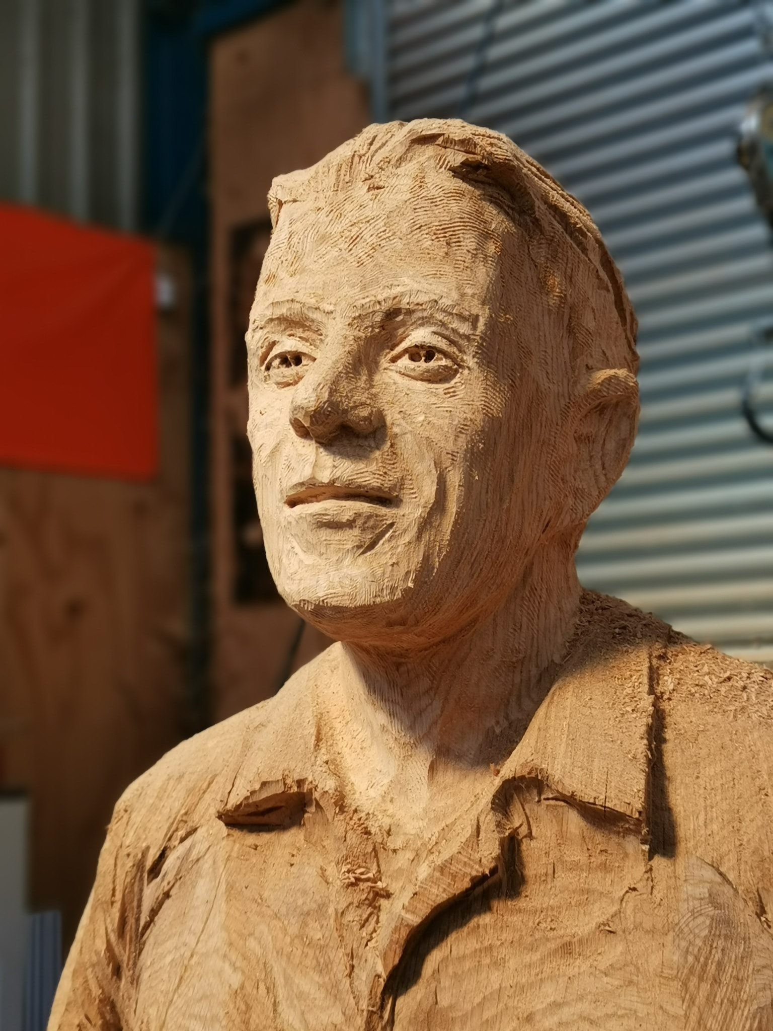 a close up of Billy Houliston's face carved in oak by simon o'rourke. The face is coarsely textured and demonstrates the impact of some of Simon's favourite tools for carving faces