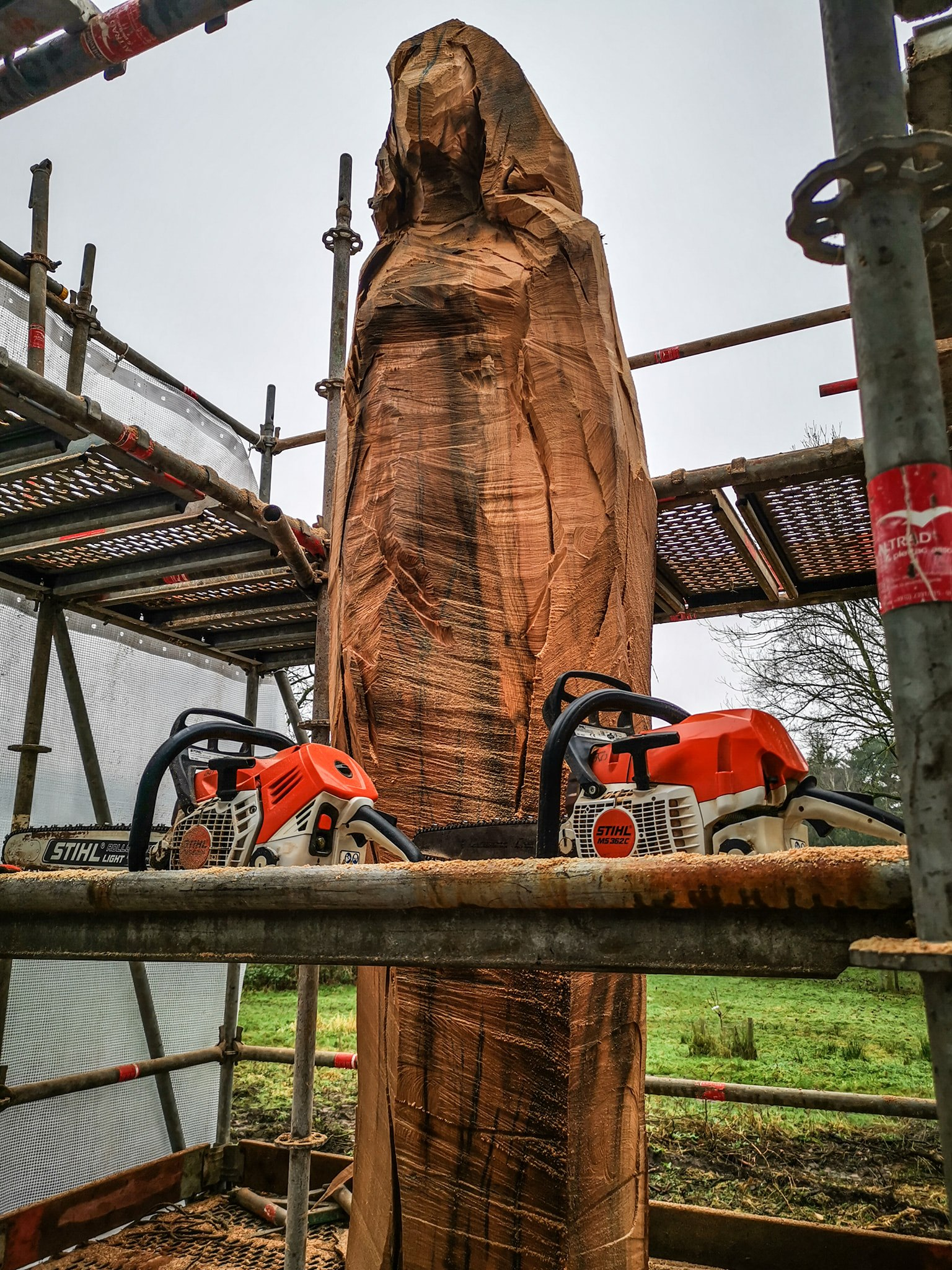 3m tree trunk in the process of being carved into a sculpture of a woman. She is surrounded by scaffolding, and two stihl chainsaws used for carving are photographed in front of the work in progress. Sculpture is the Marbury Lady by Simon O'Rourke, and the photograph is to show his favourite tools for carving faces.