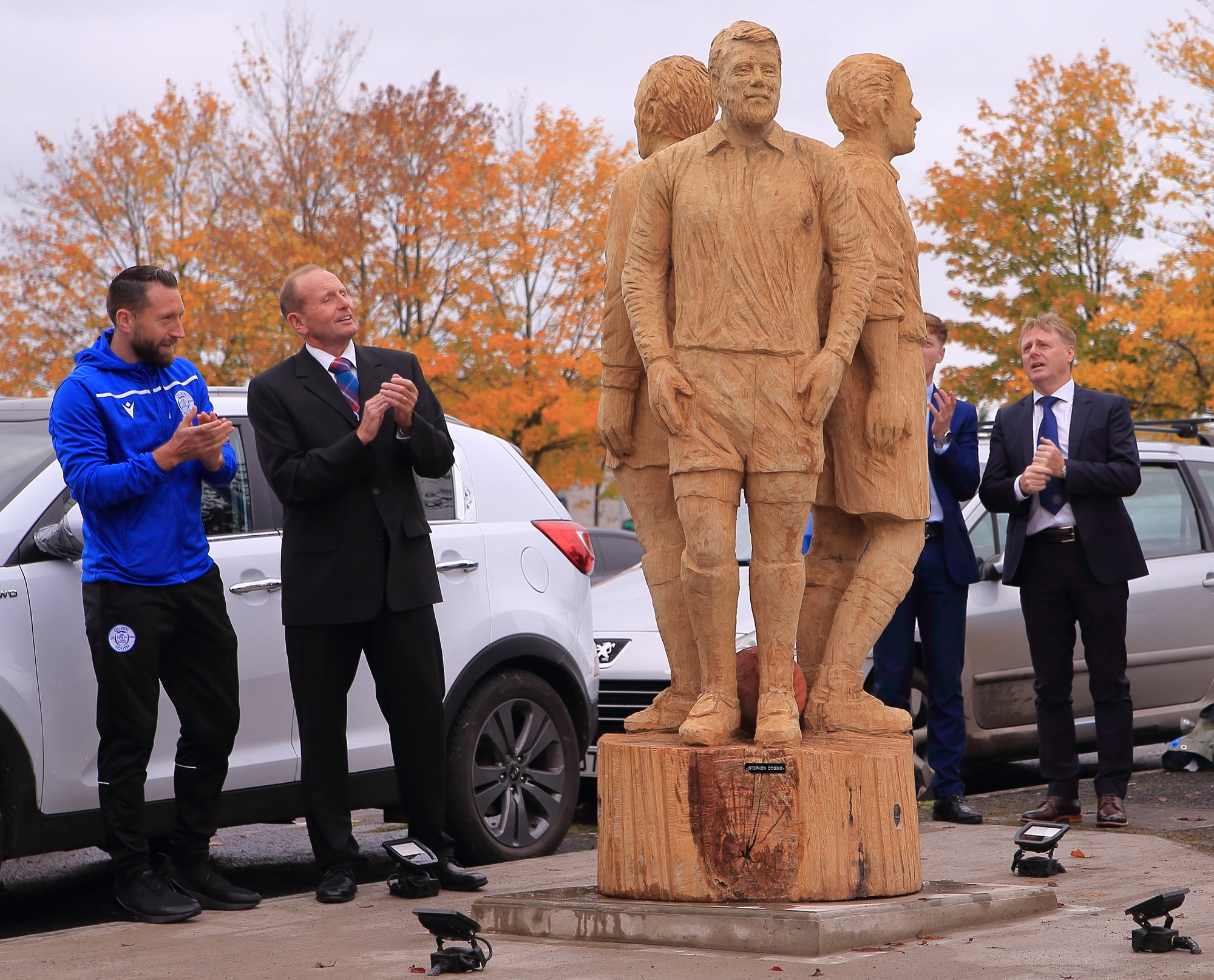 sporting sculptures made by simon o'rourke. Photo shows sculpture of three soccer players standing back to back with onlookers admiring the piece