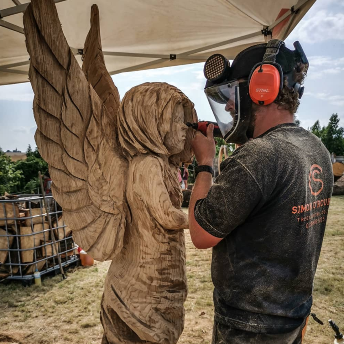 Sculptor Simon O'Rourke carving a wooden fairy at the Englihs Open CHainsaw competition