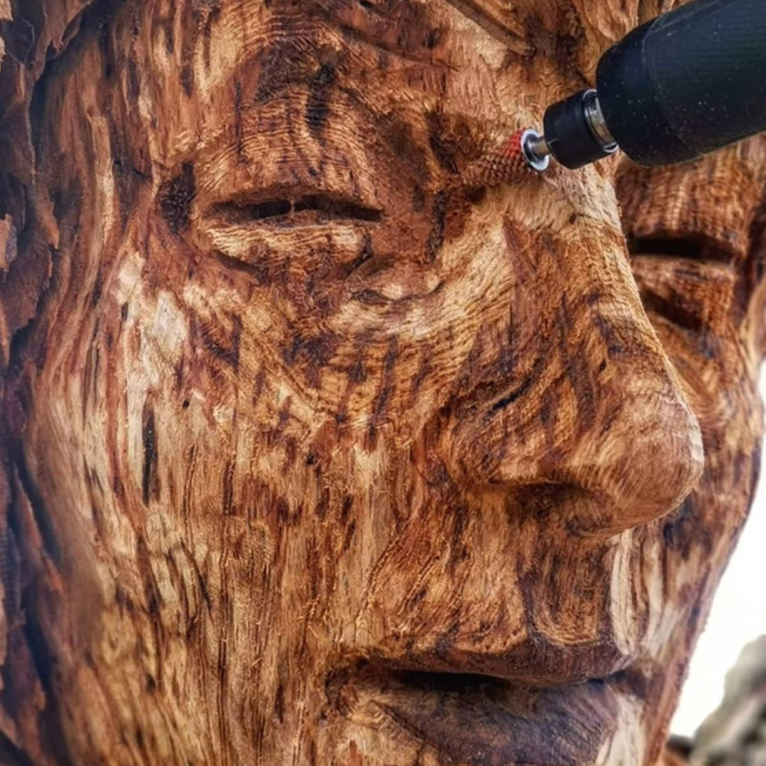 close up of simon o'rourke using a fine taper bit to shape the face of a female sculpture. the bit is one of his favourite tools for carving faces.