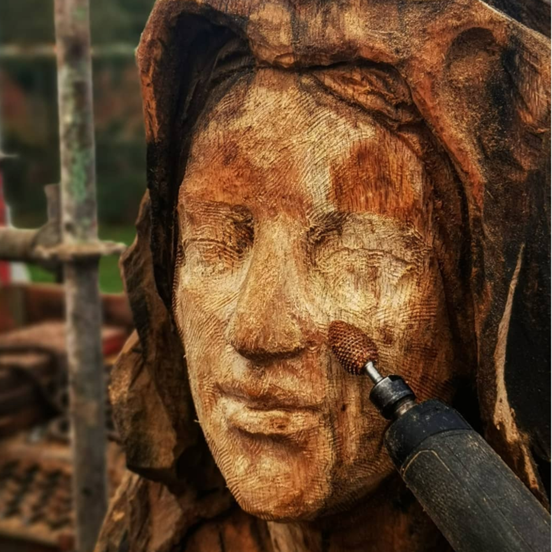 close up of a sculpture in process. the sculpture is a female face created by simon o'rourke and her face is being detailed using a daburrtooth flame bit, one of Simon's favourite tools for carving faces.