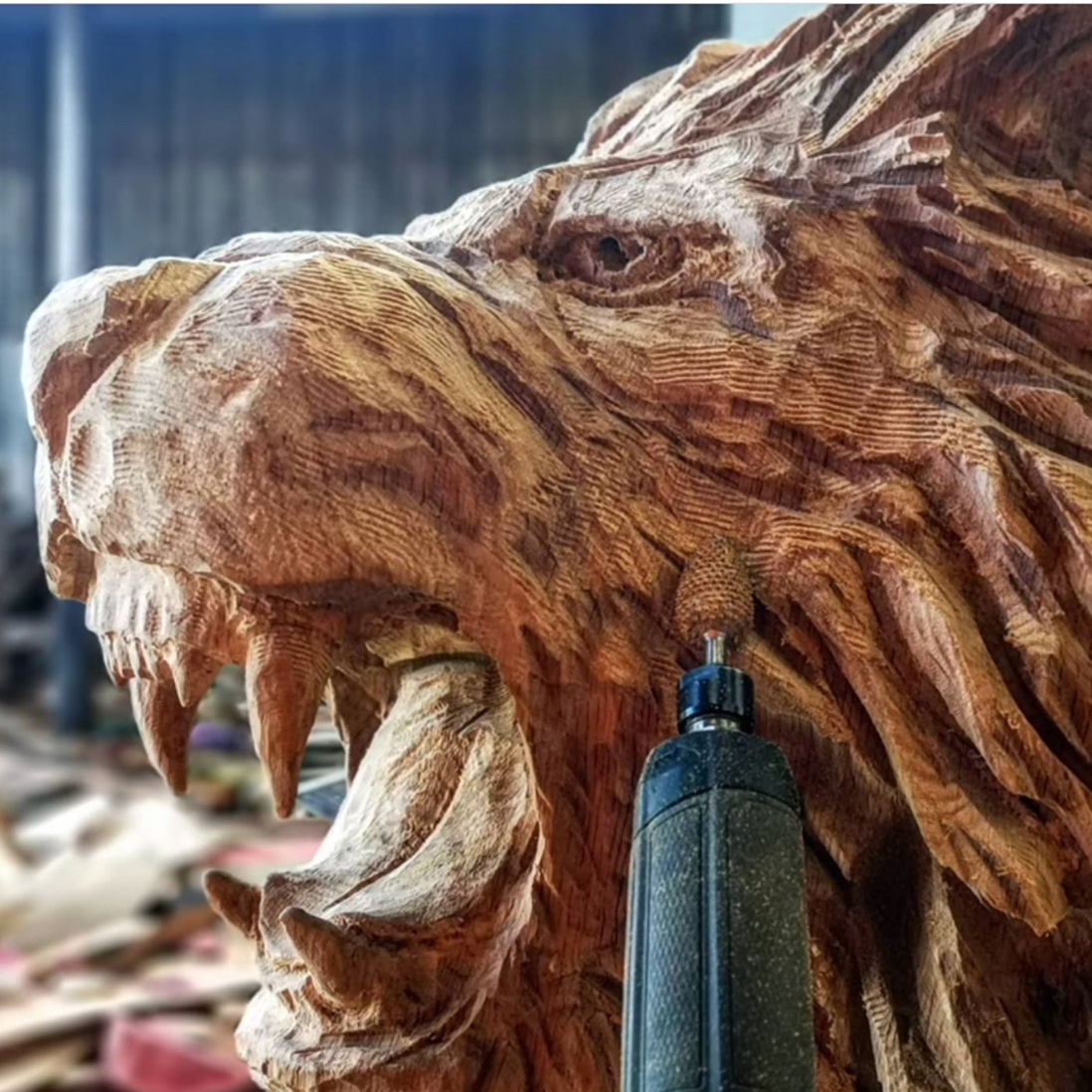 a large coarse flame bit is being used by simon o'rourke to create texture in the mane of a lion sculpture