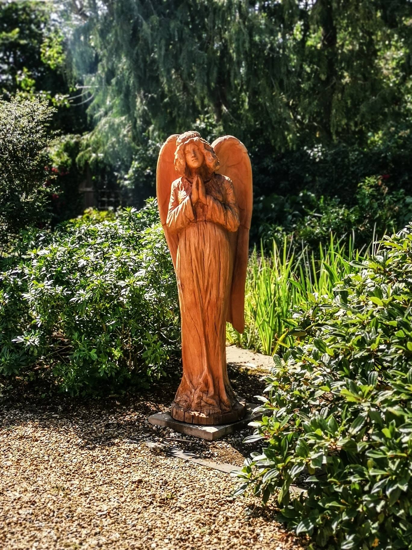 angel sculpture by simon o'rourke stands surrounded by greenery. The angel has 'praying hands' and a serene expression.