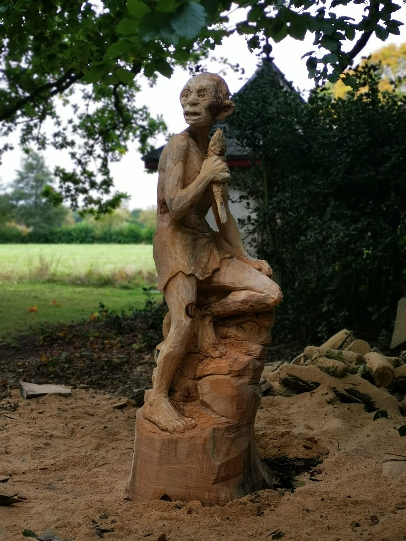 Sculpture of Gollum carved into a standing tree trunk, surrounded by the gardens at Poulton Hall. Sculpture is the work of chainsaw carving artist Simon O'Rourke