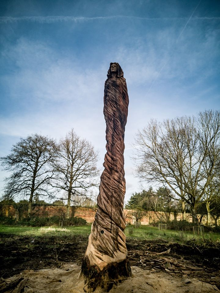 what to do with a diseased tree? photo shows an elm trunk transformed into a sculpture of a ghostly lady, standing in the grounds of marbury park