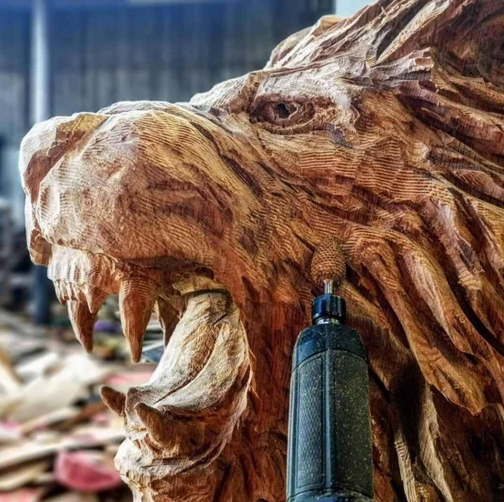 Tips for carving big cats: SImon O'Rourke uses a saburrtooth flame burr bit to create texture on a lion's face. Burr bits can be part of basic kit for starting chainsaw carving but aren't essential.