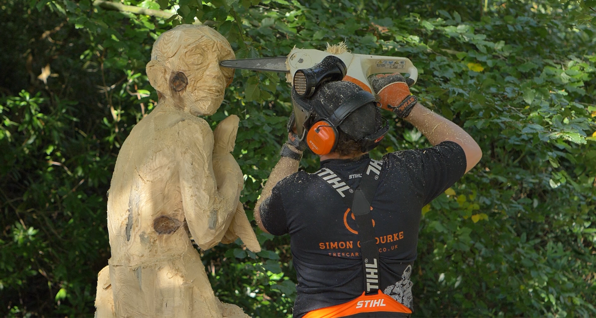 process of creating the gollum sculpture: photo shows simon o'rourke using a chainsaw to create the head shape of gollum's head from a monkey puzzle stump
