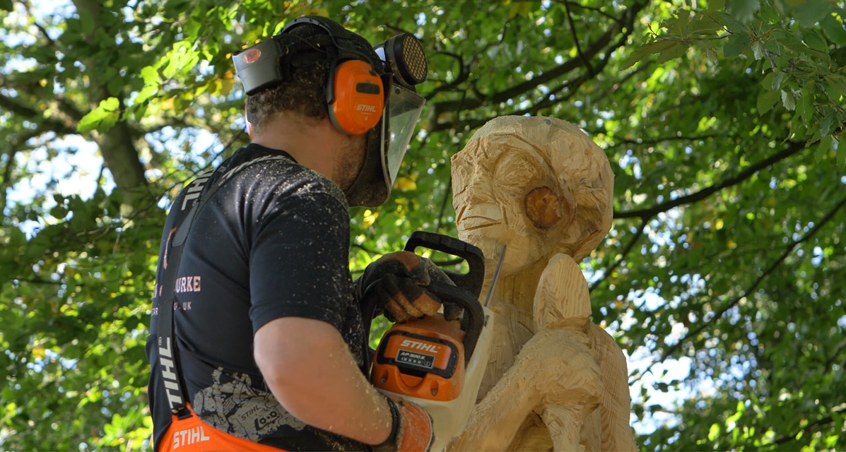 process of creating the gollum sculpture: simon o'roruke uses a stihl msa200c chainsaw to add facial features to the sculpture