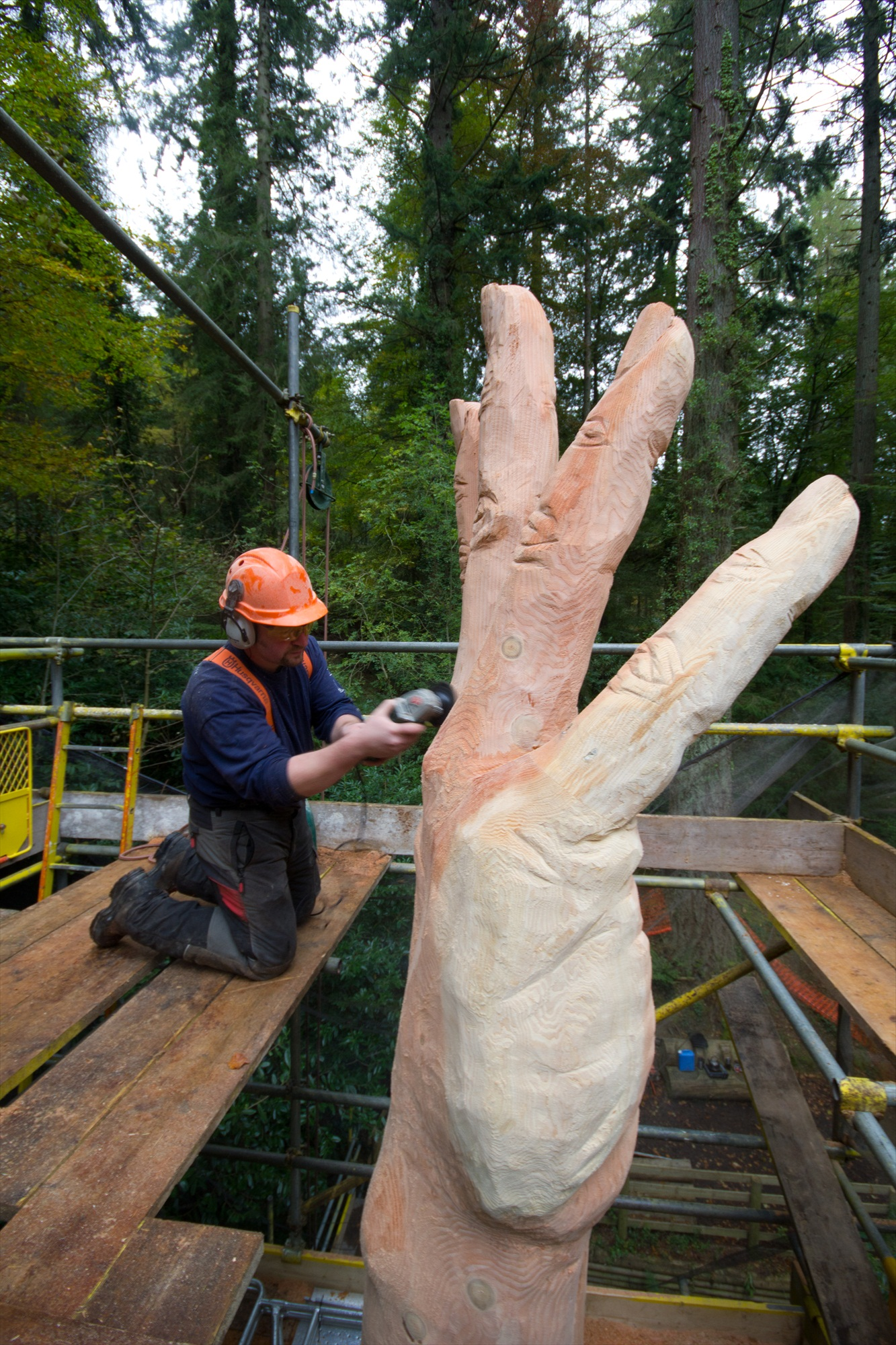 Simon O'roruke kneels in front of a giant hand carved into a tree trunk. He is using an angle grinder to add texture to the sculptire 'The GIant Hand of Vyrnwy'